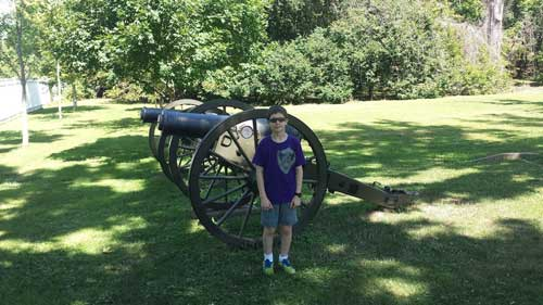Boy standing in front of a cannon